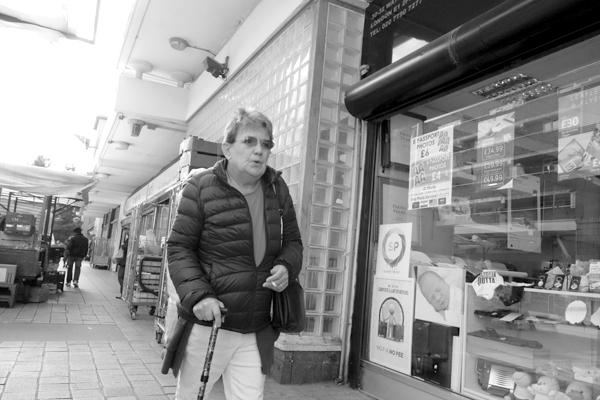 Woman with a walking stick. Watney Market. East London 2017.