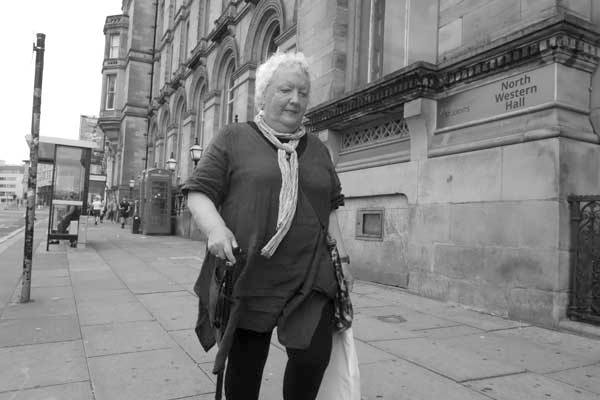 Woman with a walking stick. Lime Street. Liverpool 2017.