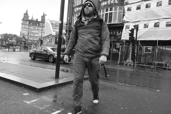 Man wearing a hood in the rain. Lime Street. Liverpool September 2017.