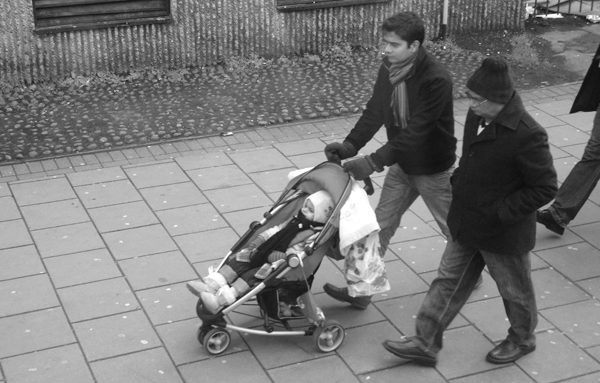 Man with a pushchair.Mile End Road. East London March 2010.