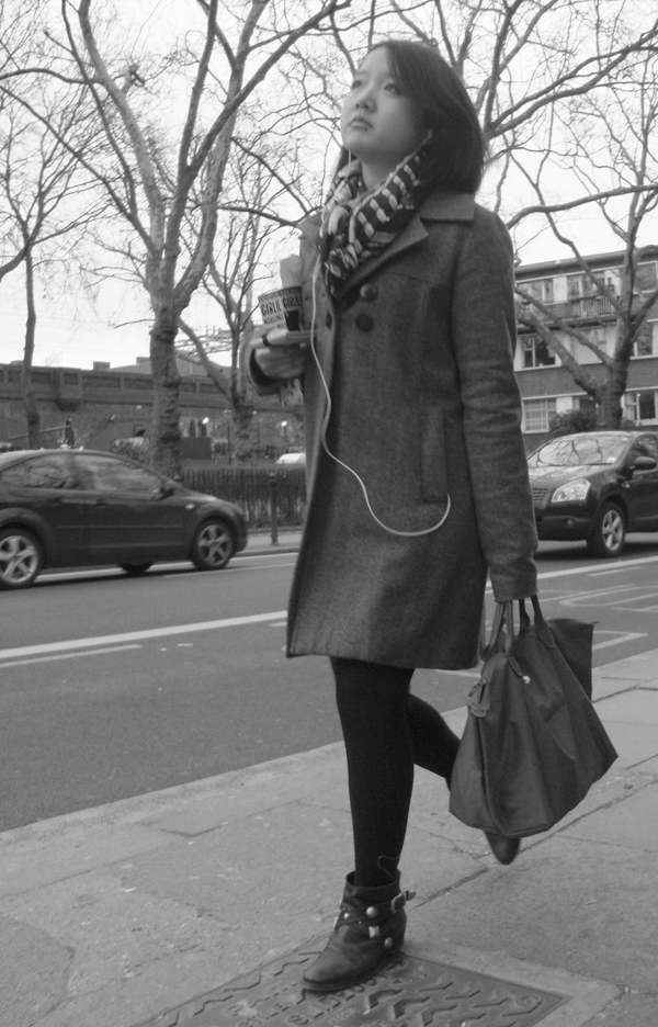 Woman passing a bus stop. Cambridge Heath Road. East London 2010.