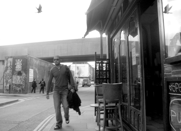 Man wearing sun glasses & a bird. Brick Lane 2010.
