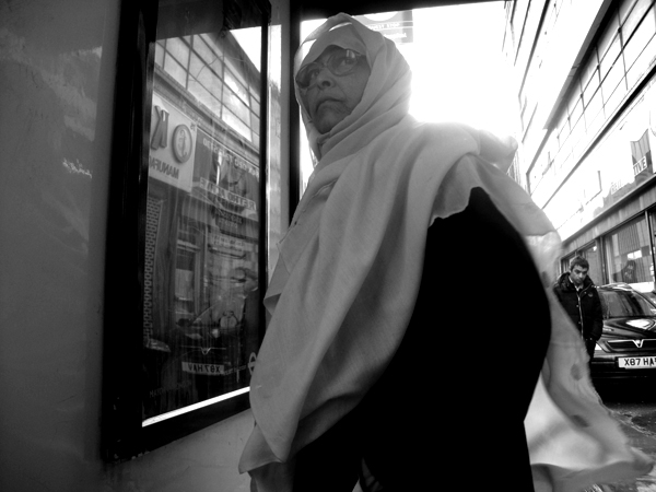 Woman at a bus stop. Bethnal Green Road. East London 2010.