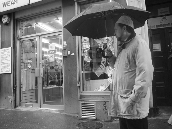 Man with an umbrella. Bethnal Green Road. East London 2010.