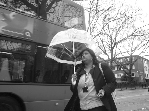 Woman with an umbrella passing a bus stop. Cambridge Heath Road. East London 2010.