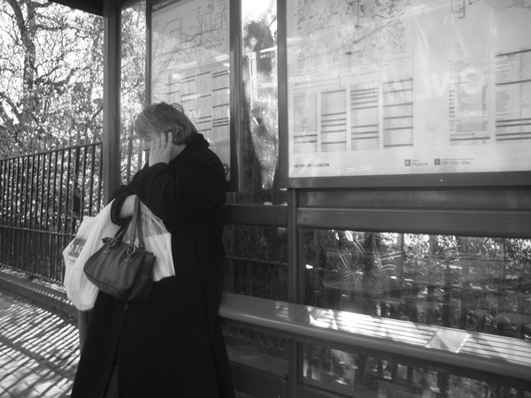 Woman at a bus stop. Cambridge Heath Road. East London 2010.