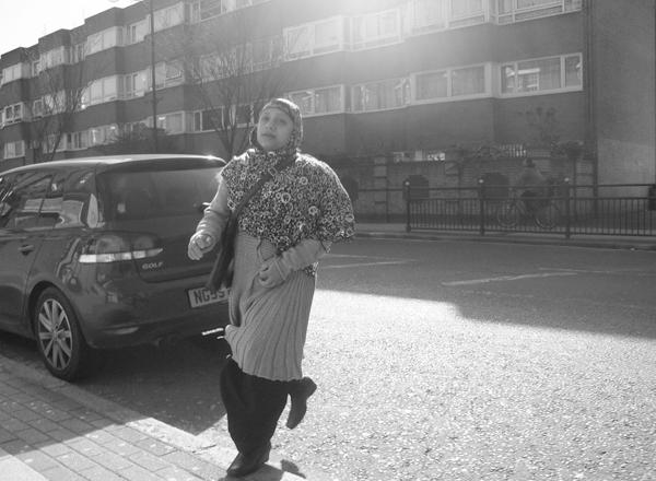 Woman crossing the road. Roman Road. East London 2010.