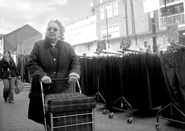 Woman with a shopping trolley. Roman Road. East London 2010.