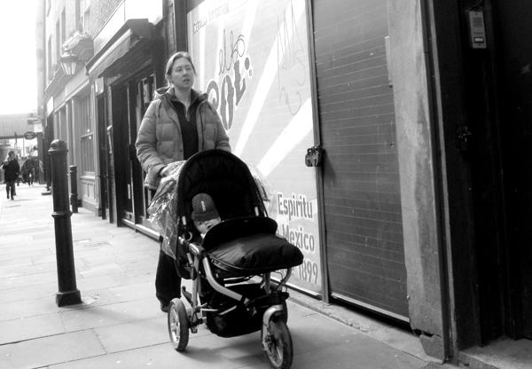 Woman with a push chair. Brick Lane 2010.