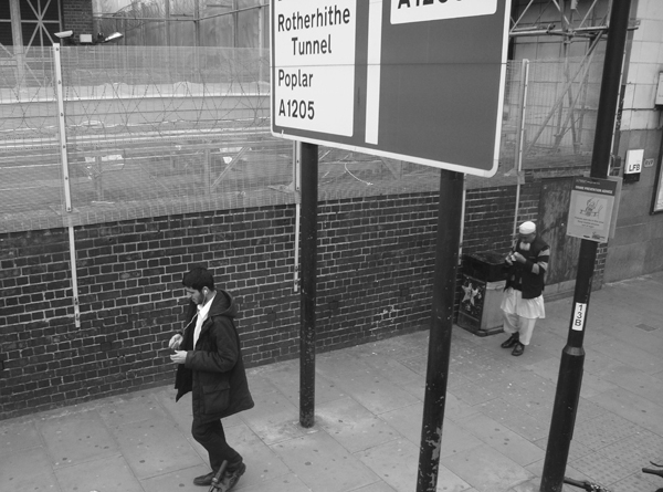Man with headphones. Near Mile End Station. Mile End Road. East London 2010.