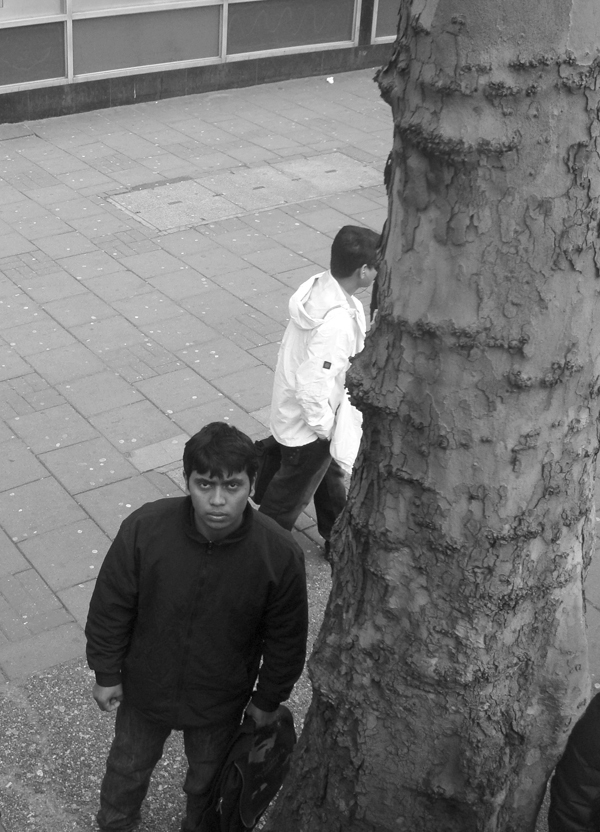 Next to a tree. Whitechapel Road. East London 2010.