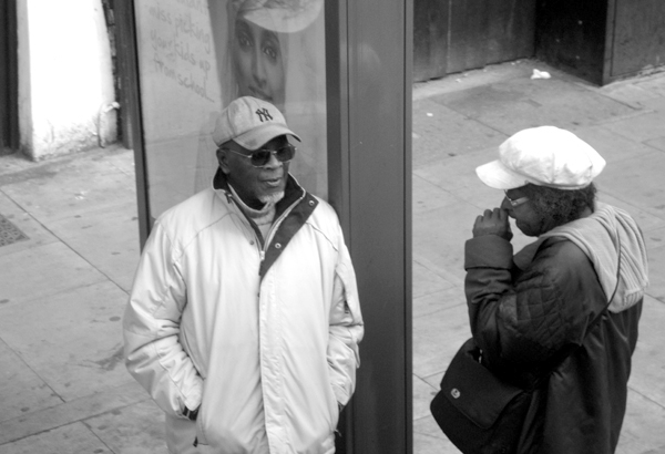 Conversation at a bus stop. Mile End Road. East London 2010.