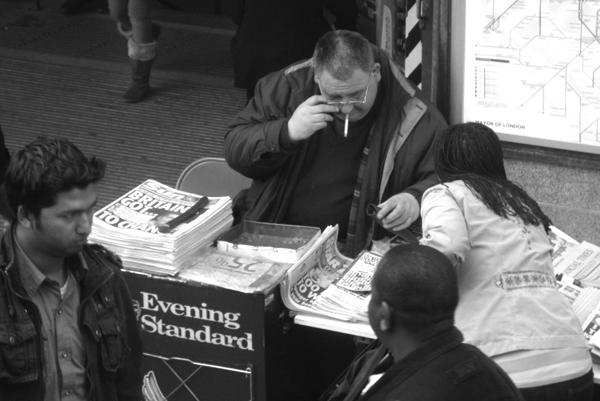 Newspaper seller, Mile End underground station. East London 2010.
