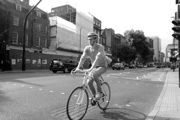 Cyclist on Whitechapel High Road. East London 2017.