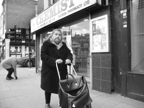 Woman with a trolley bag. Commercial Street. East London, March 2010.