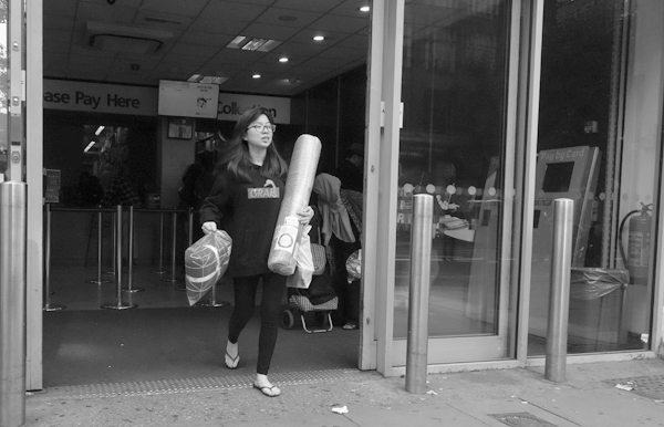 Emerging from a shop. Whitechapel High Road. East London 2017.