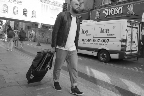 Man with some luggage on Brick Lane. East London 2017.