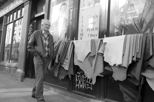 Man passing a leather shop on Cheshire Street. East London 2017.