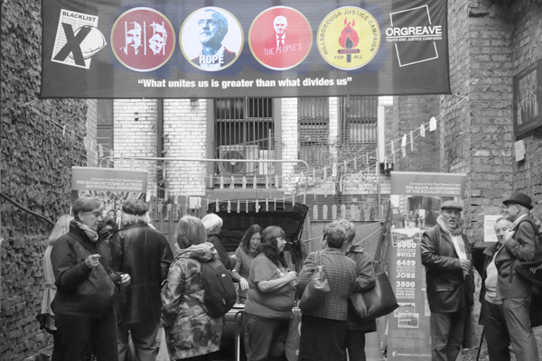 """Visitors underneath a banner that reads """"What unites us is greater than what divides us"""". Temple Street Liverpool 2017."""