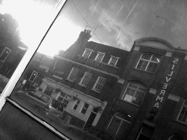 Reflections at a bus stop. Mile End Road. East London, June 2007.