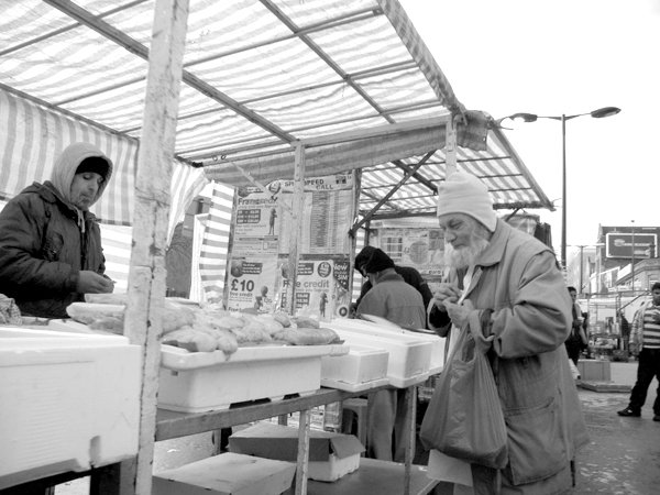 Buying fish. Whitechapel market. East London 2010.