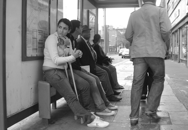 Waiting at a bus stop on New Road. East London, August 2008.