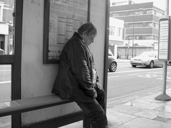 Waiting at a bus stop on Commercial Road. East London August 2008.