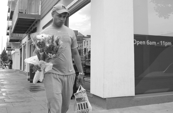 Man with flowers on Commercial Road. East London August 2008.