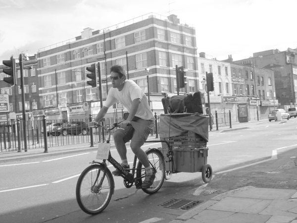 Man on a bicycle with a trailer. Commercial Road. East London August 2008.