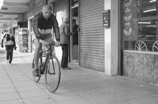 Man on a bike in Watney market. East London August 2008.