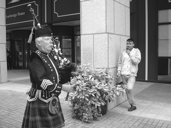 A piper plays outside Tower Hamlets Town Hall. East London August 2008.