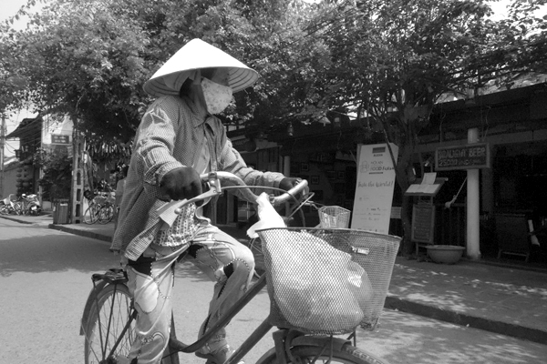 Wearing a hat and a mask on a bike. Hoi An, Vietnam 2016.