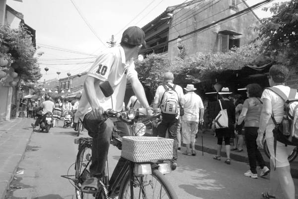 Cyclist looking behind. Hoi An, Vietnam 2016.