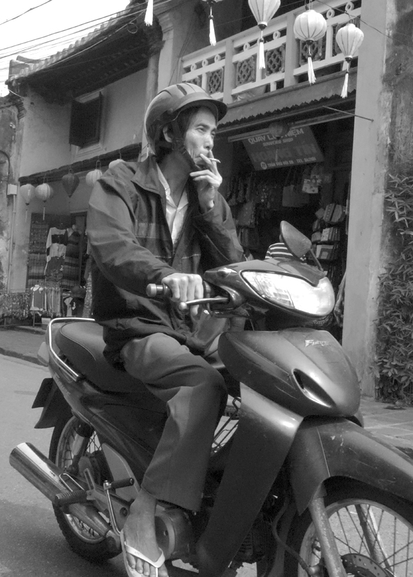 Motorcyclist smoking a cigarette. Hoi An, Vietnam 2016.
