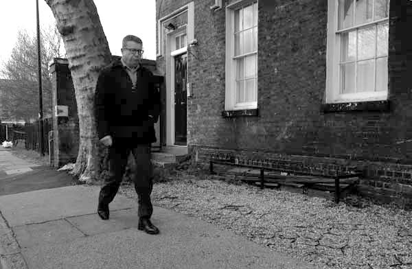 Man walking past the old church house. Buxton Street. Spitalfields 2017.