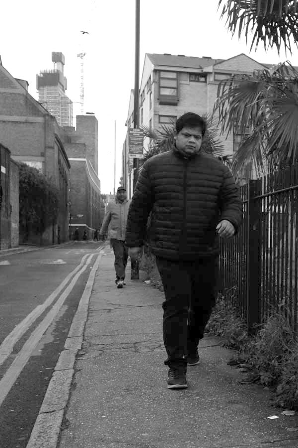 Man walking from Brick Lane down Buxton Street. Spitalfields 2017.