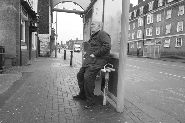 Man waiting at a bus stop on Wavertree High Street. Liverpool, December 2017.