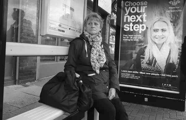 Waiting at a bus stop in Old Swan. Liverpool, November 2017.