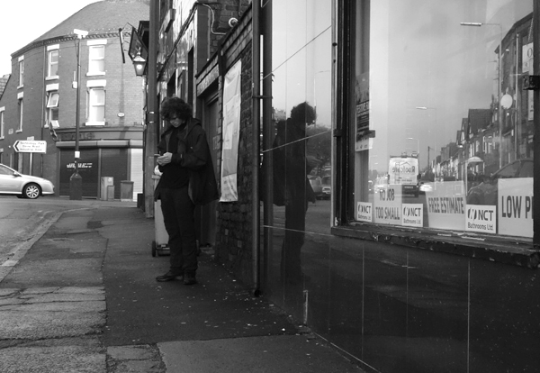 Checking a phone on Wellington Road. Liverpool January 2018.