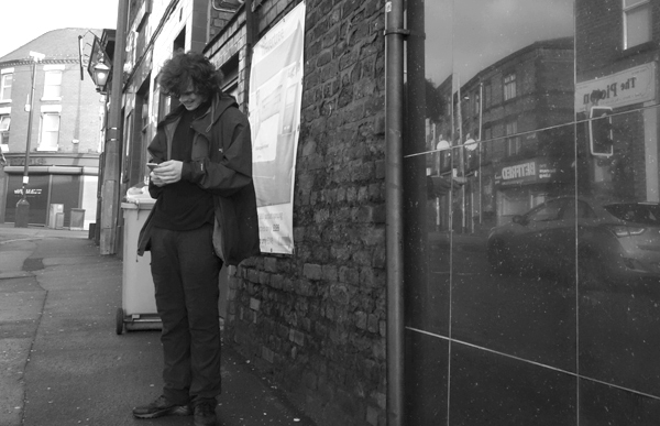 Checking the phone on Wellinfton Road. Liverpool January 2018.