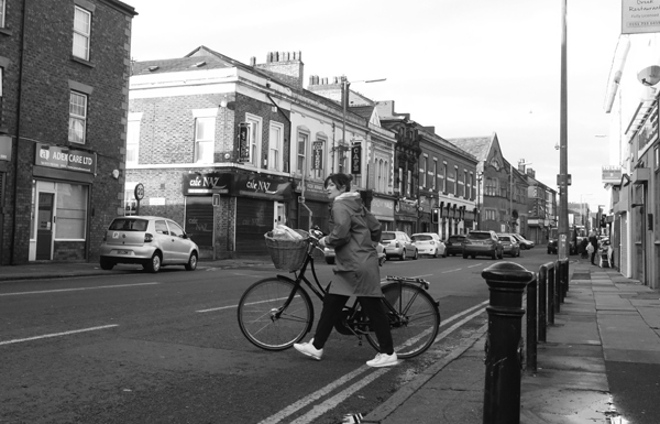 Crossing Wavertree High Street with a bicycle. Liverpool January 2018.