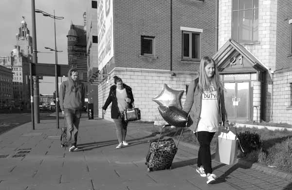 Woman with balloons & suitcase. Liverpool January 2018.