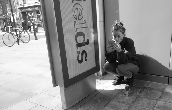 Smoking and on the phone in in Spitalfields Market. East London, September 2017.