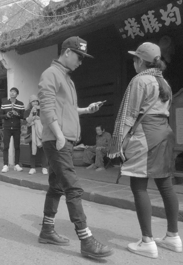 Street conversation with phone. Hoi An, Vietnam 2016.