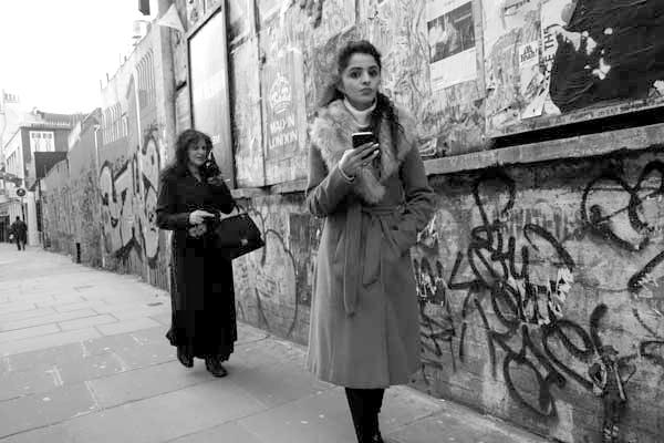 On the phone in Osborne Street (2). East London, December 2017.