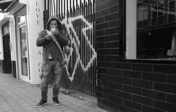 Lighting a cigarette in Osborne Street. East London, December 2017.