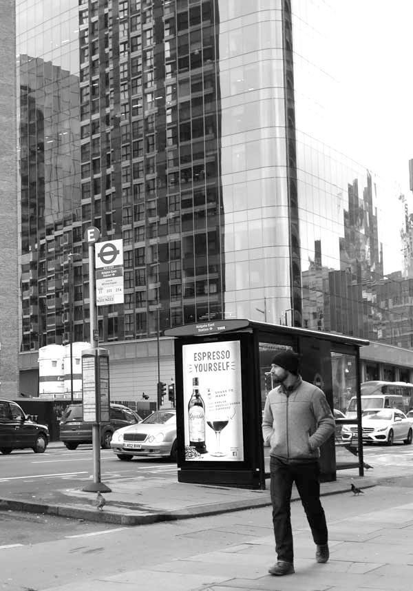Bus stop with a man wearing a woolen cap. East London, December 2017.