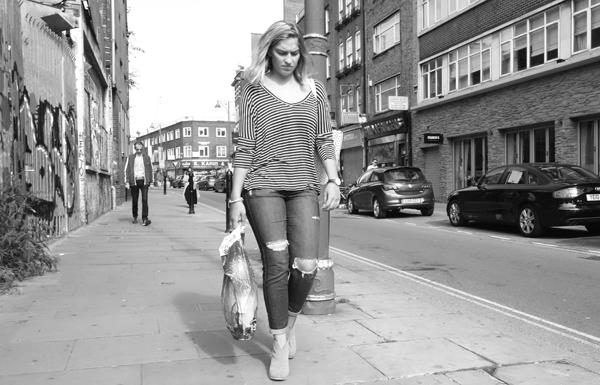 Woman wearing torn jeans on Osborne Street. East London, September 2017.