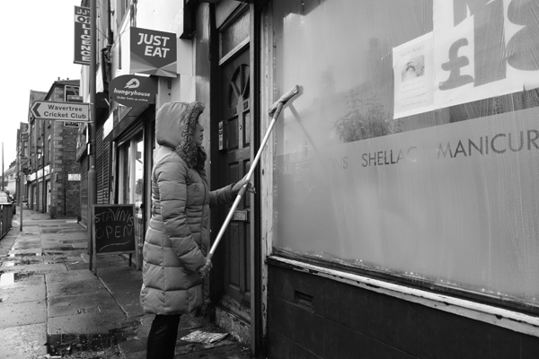 Cleaning a shop window on Wavertree High Street. Liverpool January 2018.