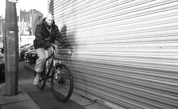 Man on a bike on Wavertree High Street. Liverpool January 2018.